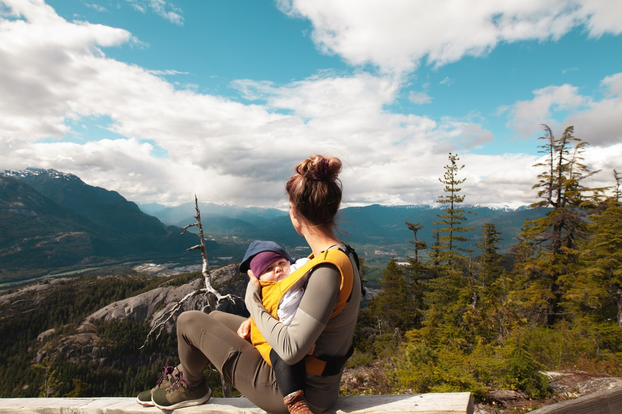 woman-carrying-baby-on-mountaintop