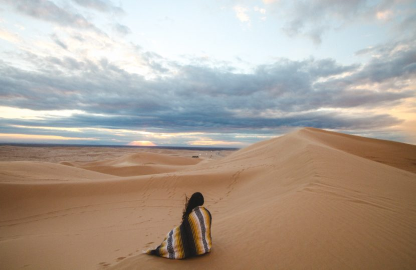 woman-sitting-on-sand-dune-watching-sunset