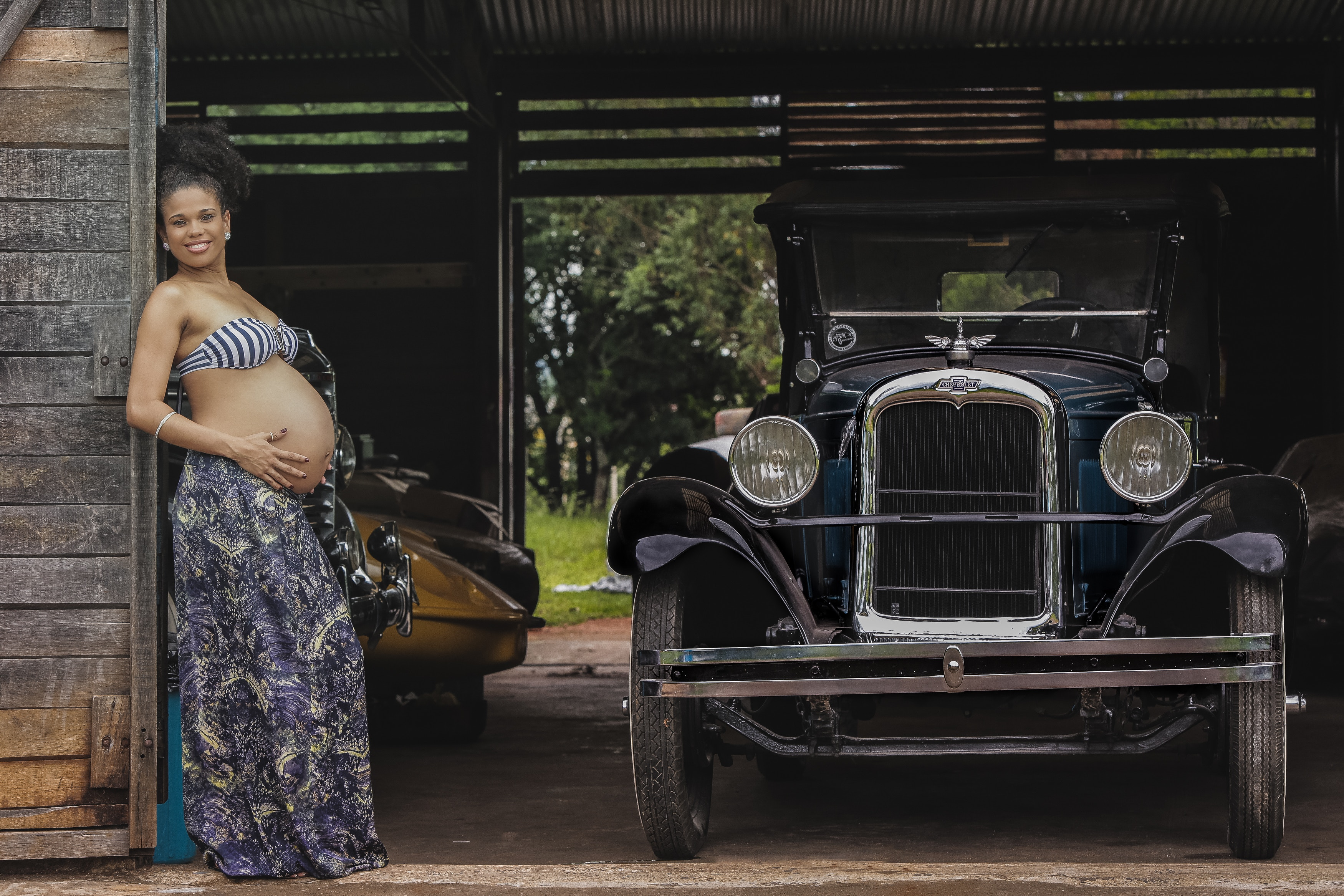boho-pregnant-woman-standing-in-garage-by-vintage-car-happy-pregnancies