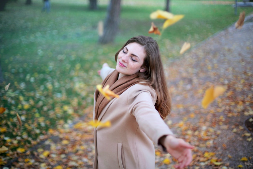 woman-smiling-under-falling-leaves-during-thanksgiving