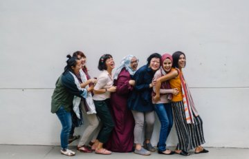 women-standing-in-a-line-laughing