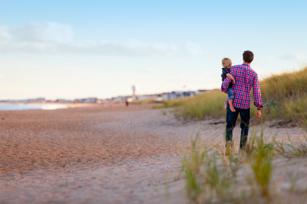 man-carrying-daughter-on-beach