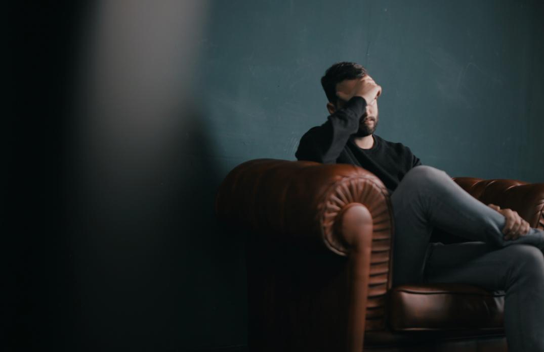 sad-man-sitting-on-sofa-alone