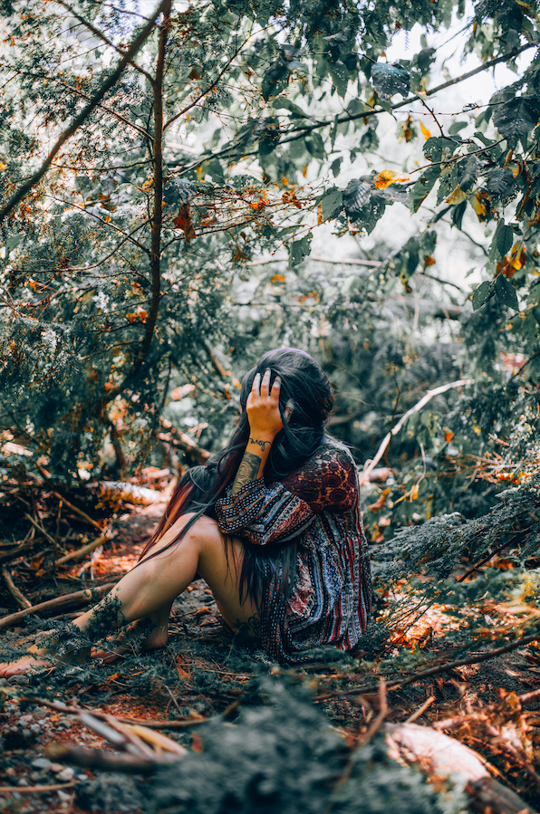 depressed-woman-sitting-on-forest-floor