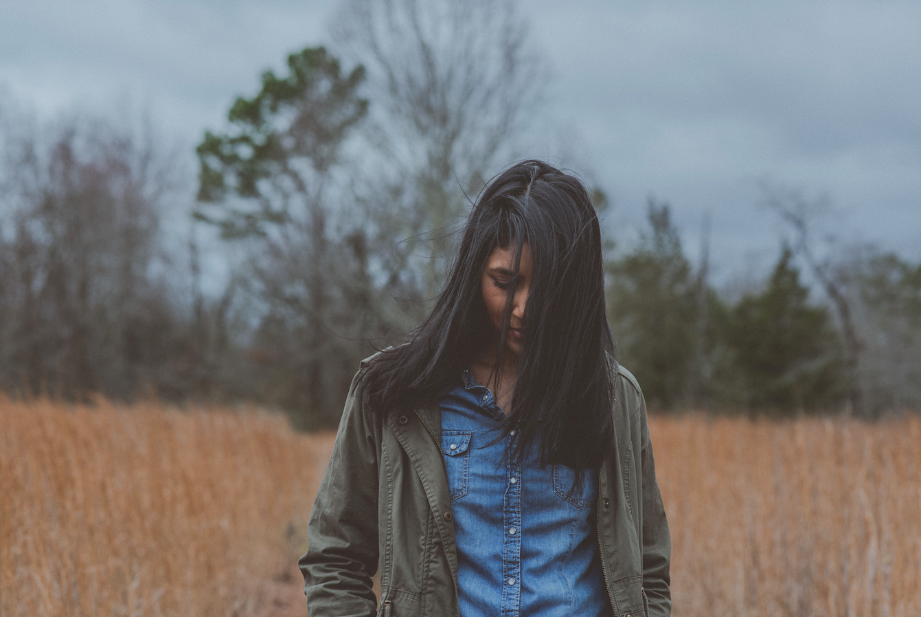 sad-woman-walking-through-field