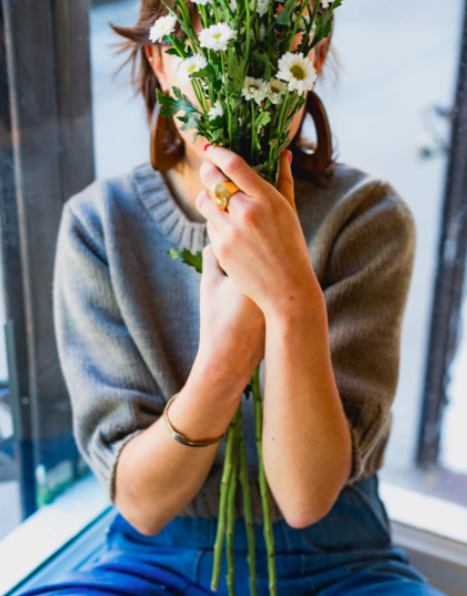 woman-holding-flowers-in-front-of-face