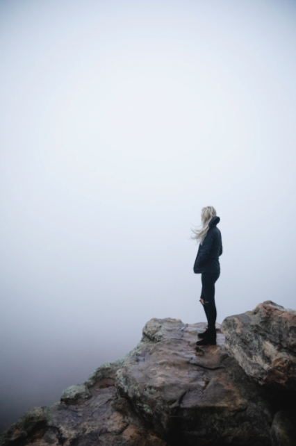 woman-standing-on-cliff-lonely