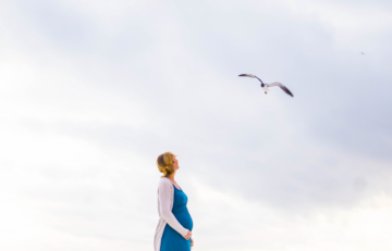 pregnant-woman-in-blue-dress-looking-at-sky-as-seagull-flies-by